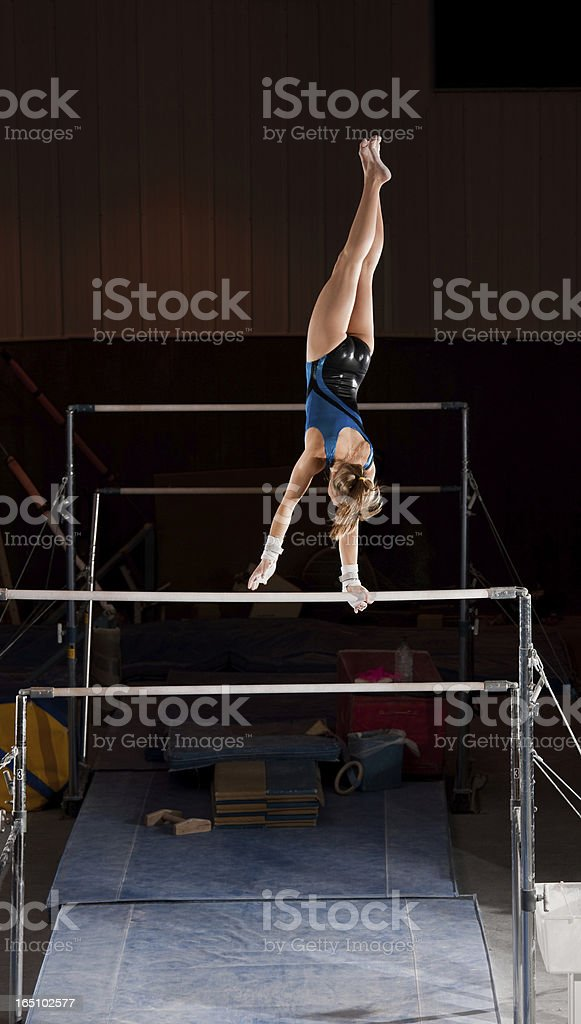 Female Gymnast On Uneven Bars stock photo