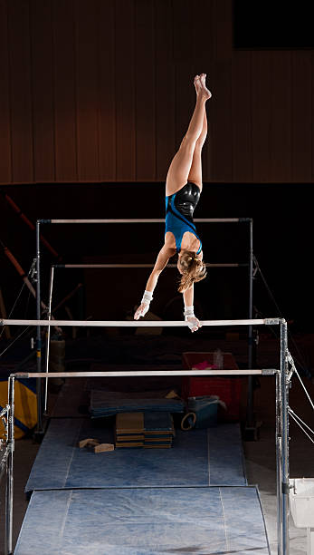 female gymnast on uneven bars - uneven parallel bars stock photos and pictures