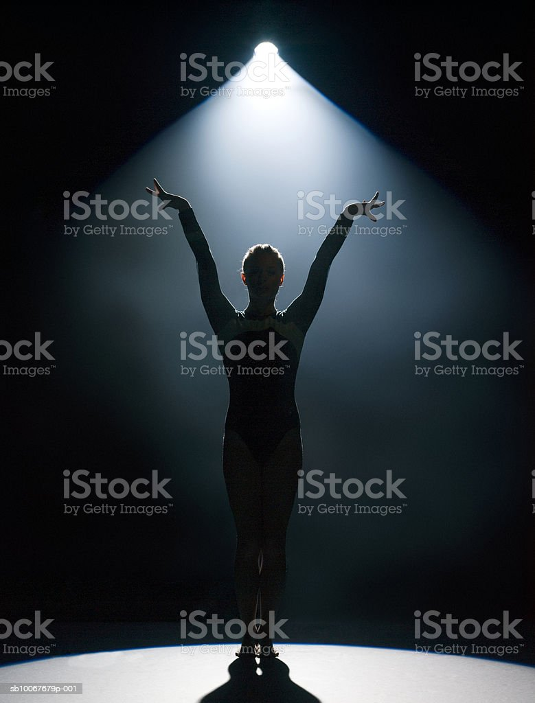 Female gymnast performing in spotlight, studio shot royalty-free stock photo