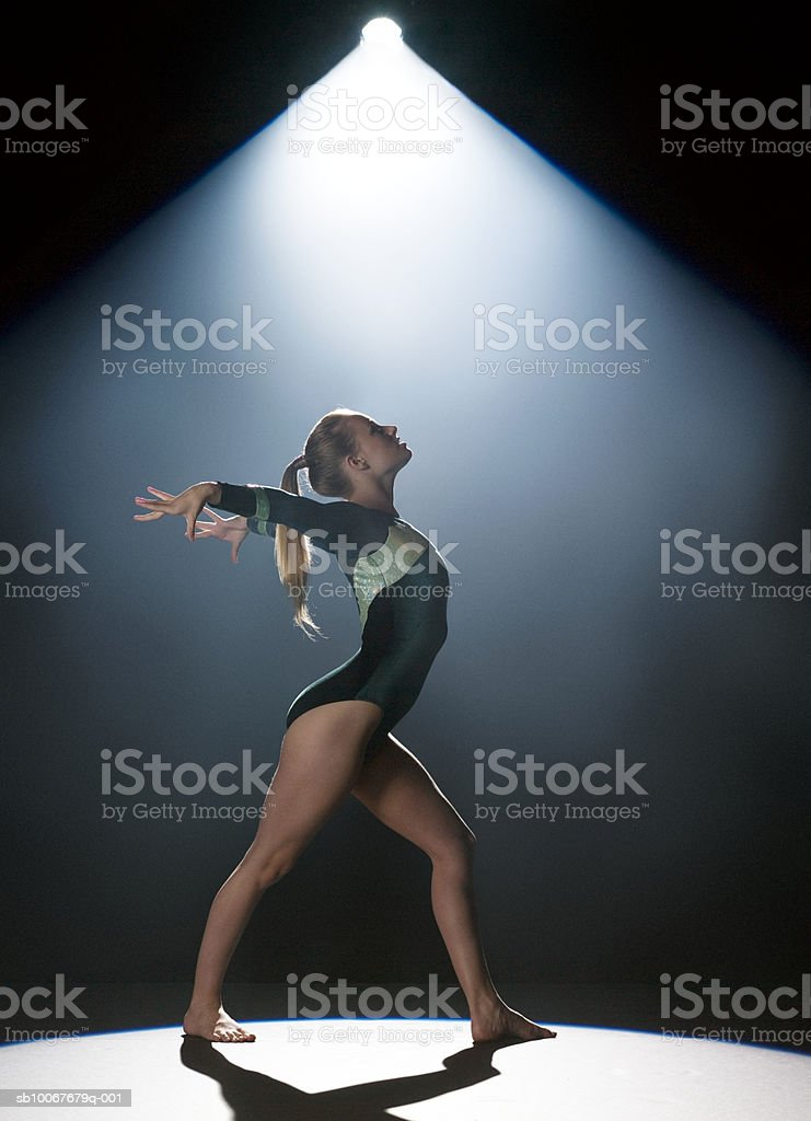Femmina ginnasta esecuzione in spotlight, Fotografia da studio foto stock royalty-free