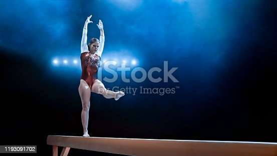 Young female gymnast performing on balance beam.