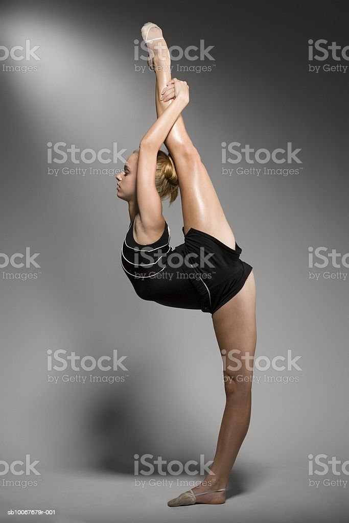 Female gymnast stretching, studio shot royalty free stockfoto