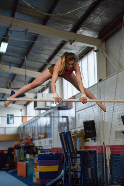 female gymnast training on bars - horizontal bar stock photos and pictures