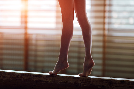istock Female gymnast walking on balance beam, low section 511869048