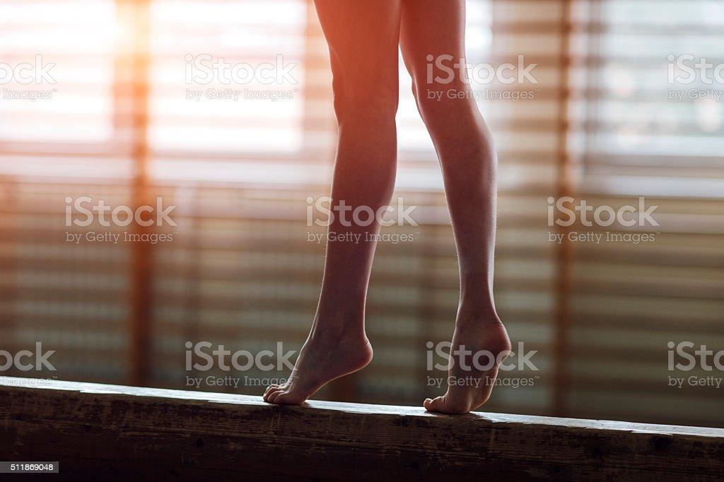 Hembra gimnasta caminando en la barra de equilibrio, bajo la sección - foto de stock