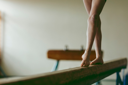 Female gymnast walking on balance beam, low section stock photo