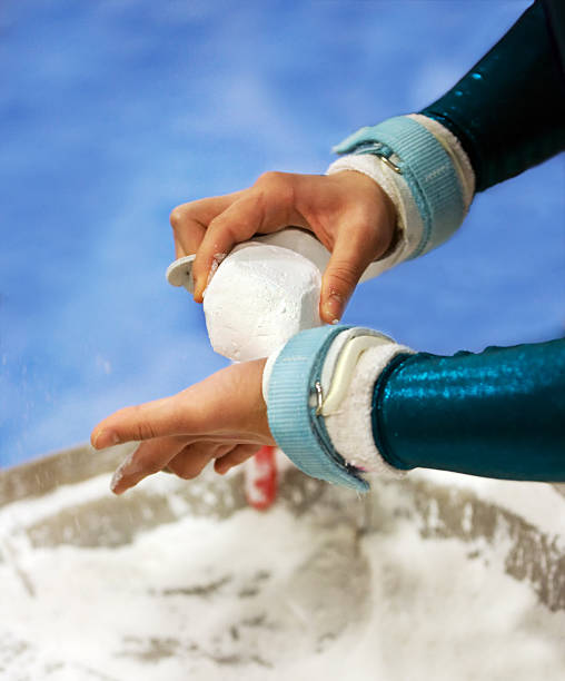 female gymnist chalking hands - uneven parallel bars stock photos and pictures
