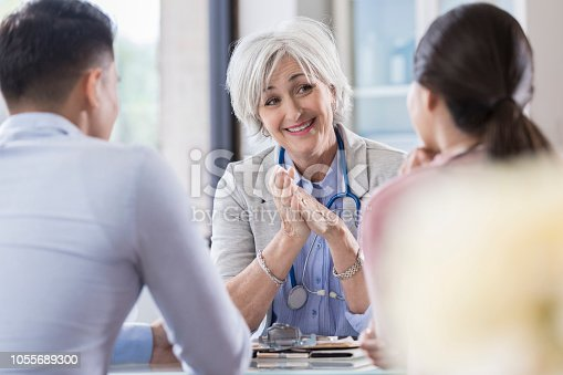 Confident senior female gynecologist talks with a young couple.