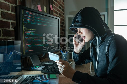 1008108222 istock photo female hacker doing phone fraud and robbery. 1041523182