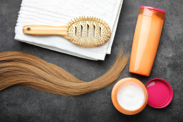 female hair, hair care products, hairbrush and towel stock photo