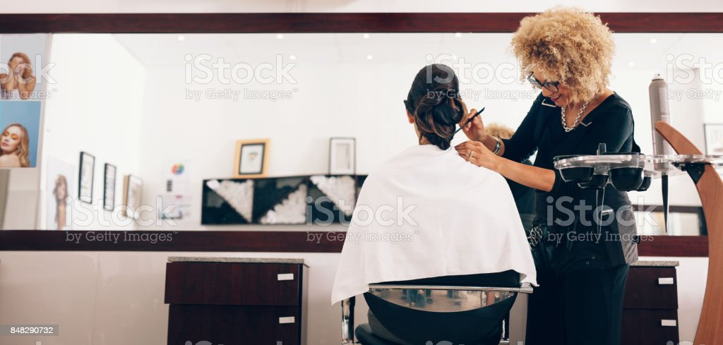 Female hair stylist working on a woman 's hair at salon stock photo