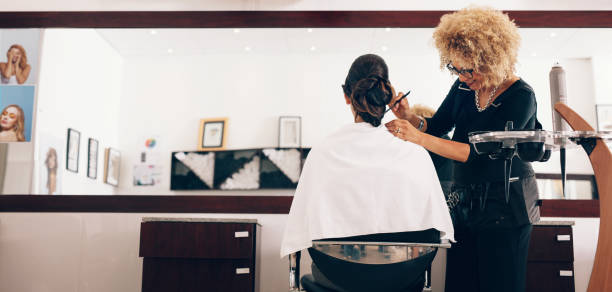 female hair stylist working on a woman 's hair at salon - beauty salon stock photos and pictures