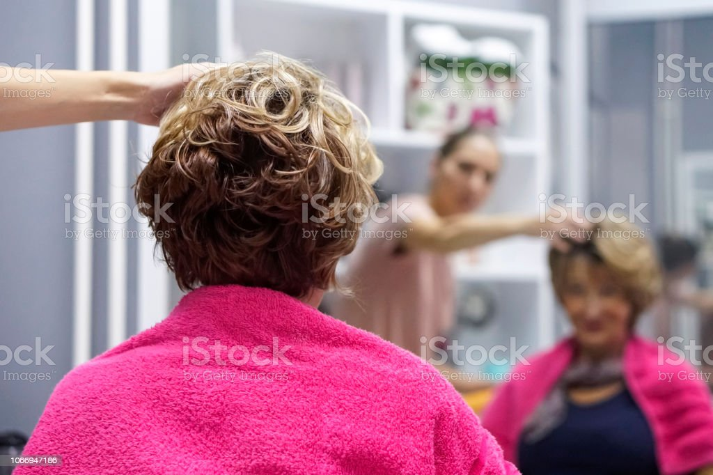 Female hairdresser and senior woman in a hair salon stock photo