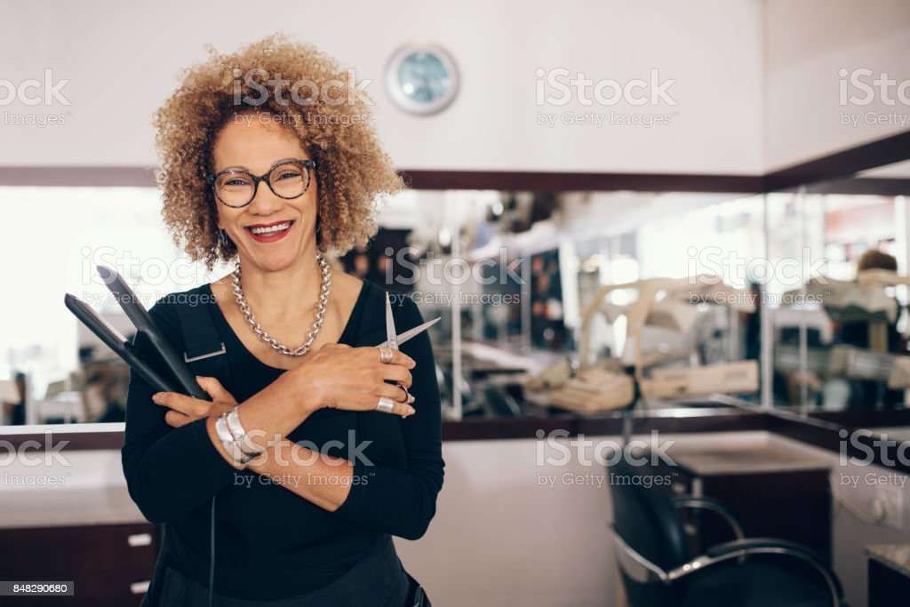 Female hairdresser at the salon holding hairdressing tools – zdjęcie