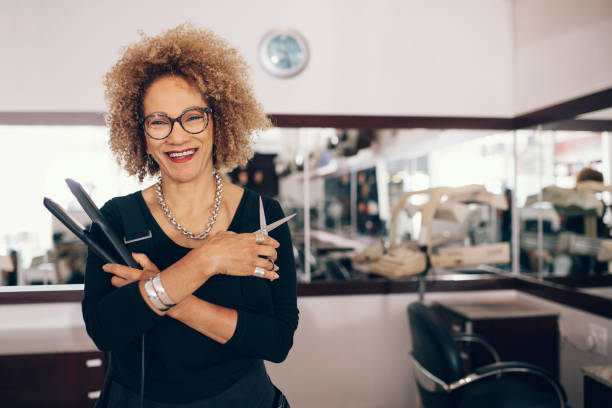 female hairdresser at the salon holding hairdressing tools - beautician stock photos and pictures