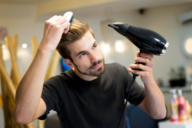 Female hairdresser combing and drying his own hair in hair salon stock photo