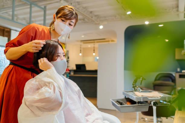 お客様に髪型についてのアドバイスを与える女性の美容師。病気予防のための保護フェイスマスクを着用した所有者と顧客 - 美容師 ストックフォトと画像