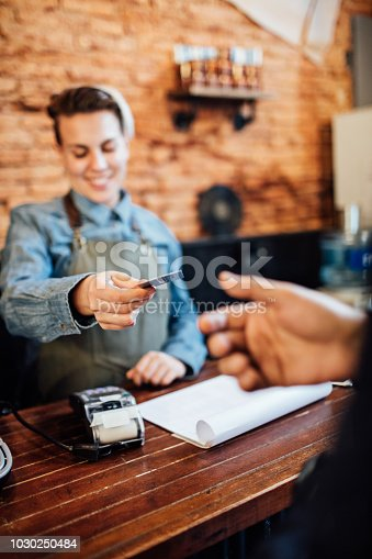 istock Female hairdresser giving credit card to customer 1030250484
