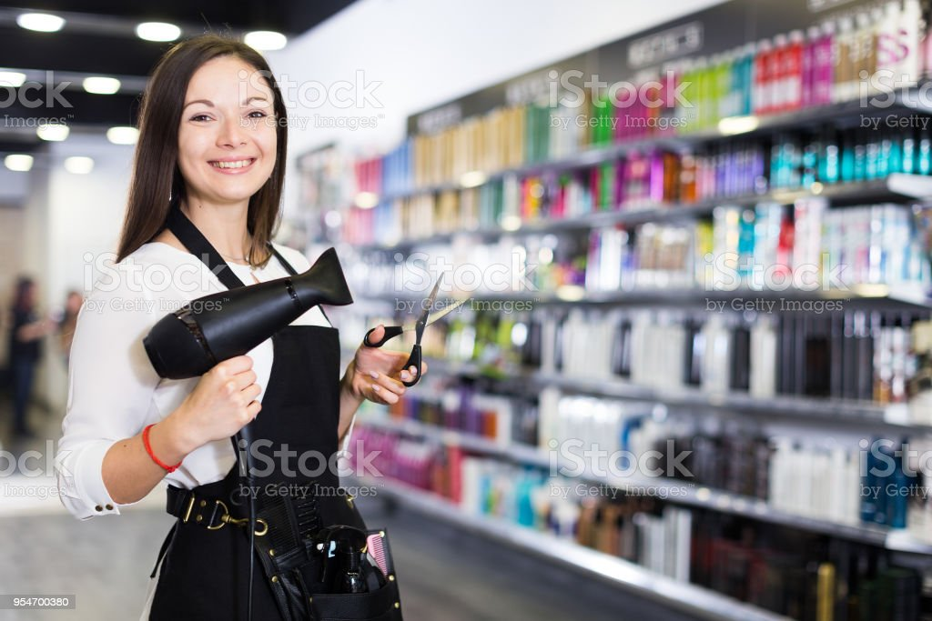 Female hairdresser in apron  holding blow dryer and hair cutters in shop stock photo