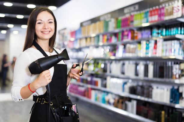 Cabeleireiro feminino no avental segurando o secador e cortadores de cabelo na loja - foto de acervo