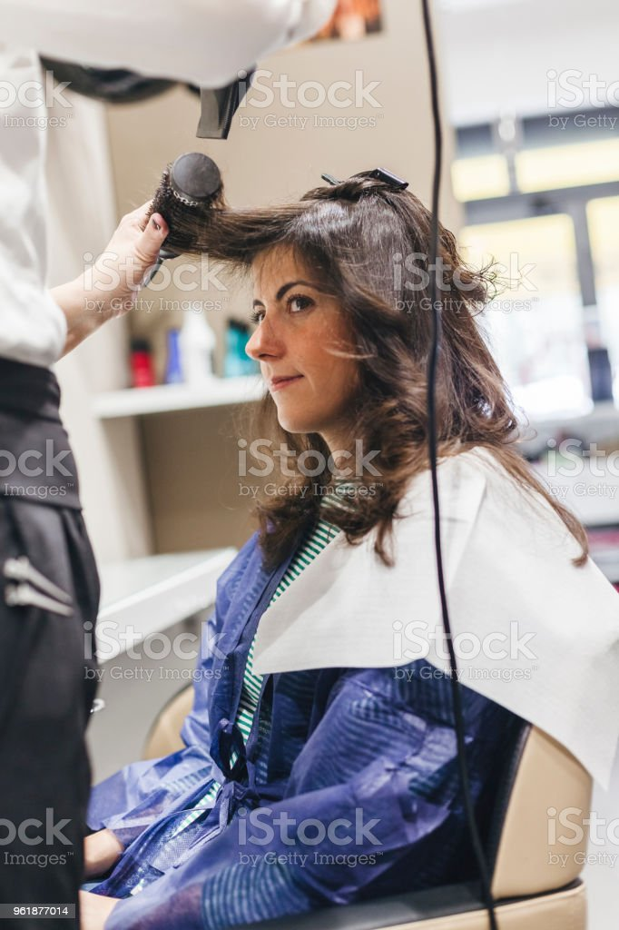 Female hairdresser making hairstyle to young woman in hair salon