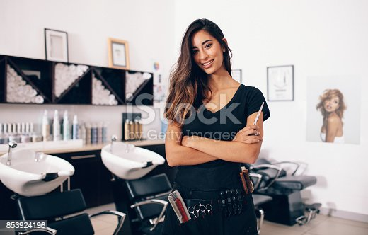 istock Female hairdresser standing in salon 853924196