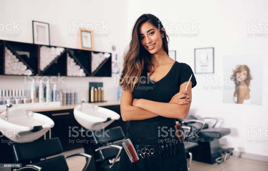 Female hairdresser standing in salon stock photo