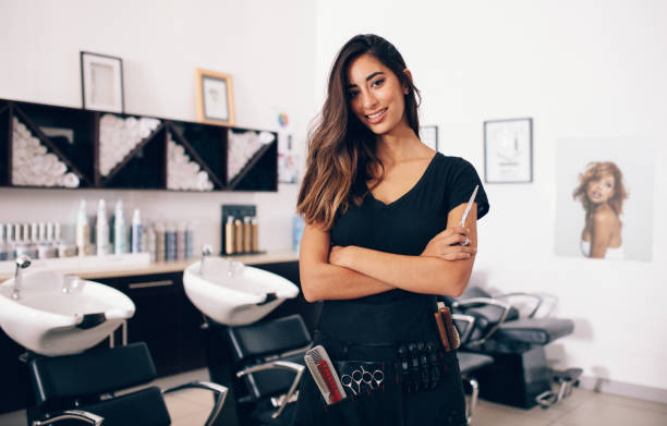female hairdresser standing in salon - beauty salon stock photos and pictures