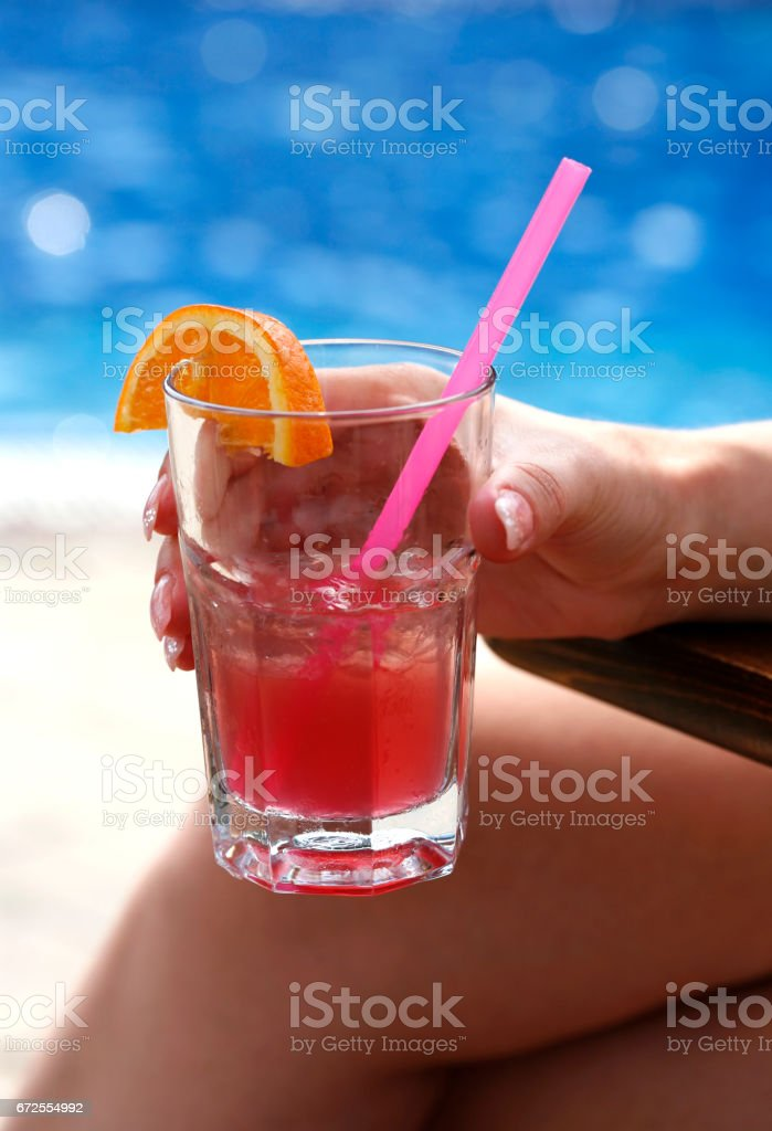 Female hand about a cocktail with an orange stock photo