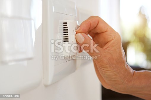 istock female hand adjusting temperature with dial on air conditioning 873392936