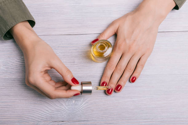 female hand applied oil on the nails - cuticle stock pictures, royalty-free photos & images