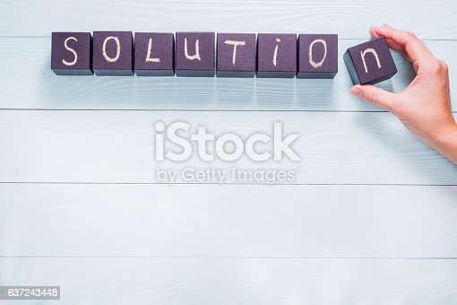 istock Female hand arrange wood letters as Solution word 637243448