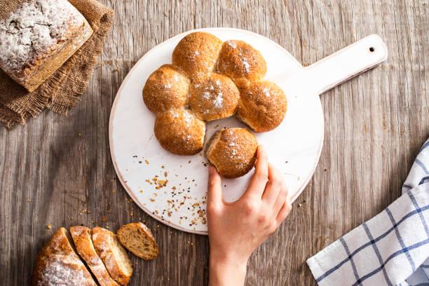 Female hand breaking freshly baked bread – Foto