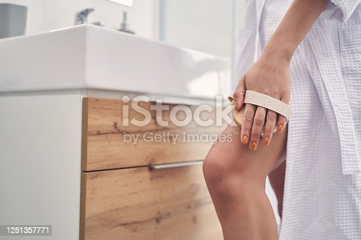 Close up of young woman hand massaging leg with lymphatic detox massage brush