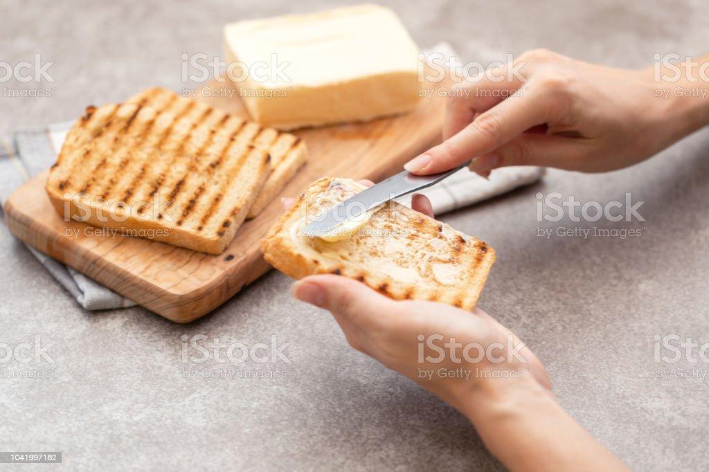 Weibliche Hand Butter Toast zum Frühstück – Foto