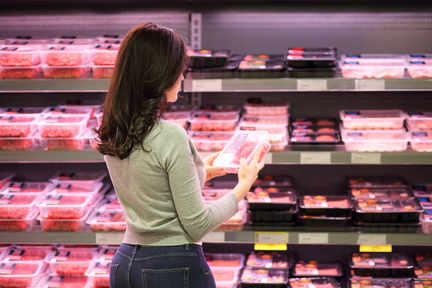 Female hand chooses pear in the store Women choosing a dairy products at supermarket. Reading product information produce aisle stock pictures, royalty-free photos & images