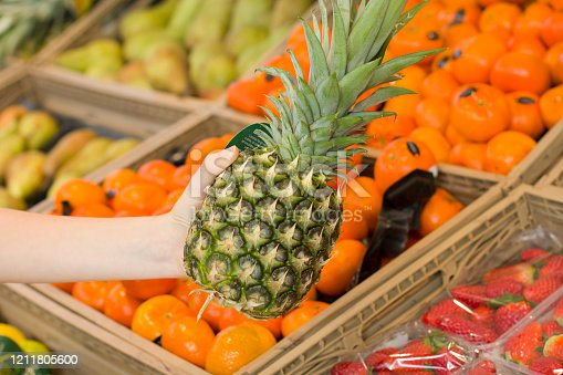 istock Female hand choosing ananas in the store. Concept of healthy food, bio, vegetarian, diet. 1211805600
