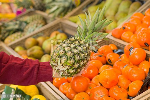 istock Female hand choosing ananas in the store. Concept of healthy food, bio, vegetarian, diet. 1211805709