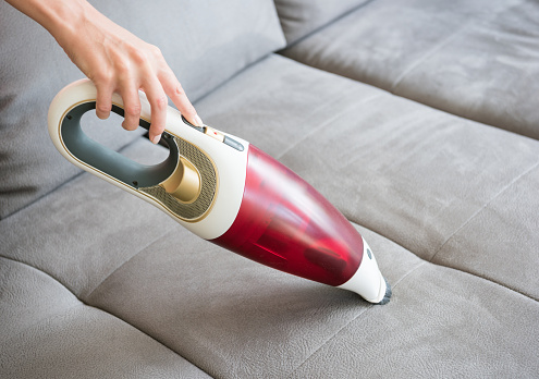 Natural female hands cleaning the sofa couch with a handheld vacuum cleaner
