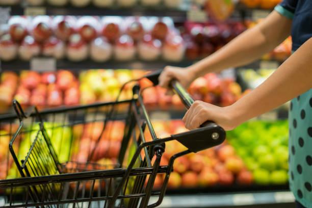 Weibliche Hand schließen sich mit Einkaufswagen in einen Supermarkt zu Fuß durch den Gang Wagen im Kaufhaus Bokeh Hintergrund, Vintage Farbe, Textfreiraum, selektiven Fokus – Foto