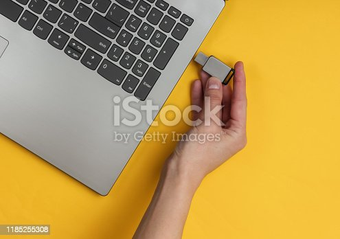 Female hand connects USB flash drive to laptop on yellow paper background. Top view