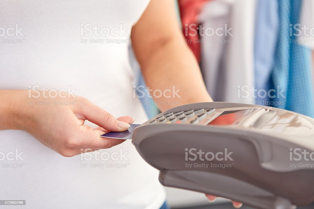 Female hand controls payment terminal stock photo
