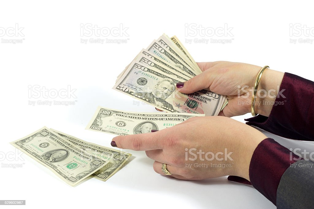 Female Hand Counting American Dollar Bills Against White Background stock photo