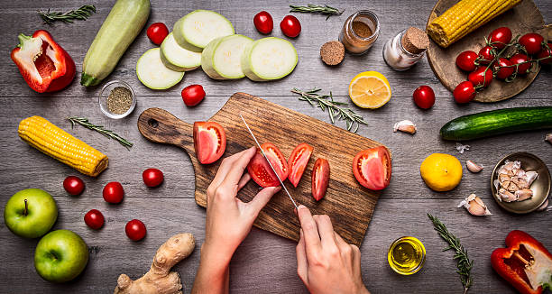 female hand cut tomatoes rustic kitchen table,vegetarian concept. - food and drink stock photos and pictures