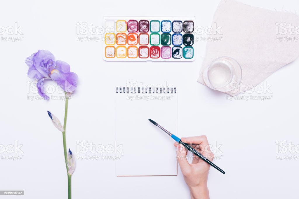 Female hand drawing in a notebook with watercolors royalty-free stock photo