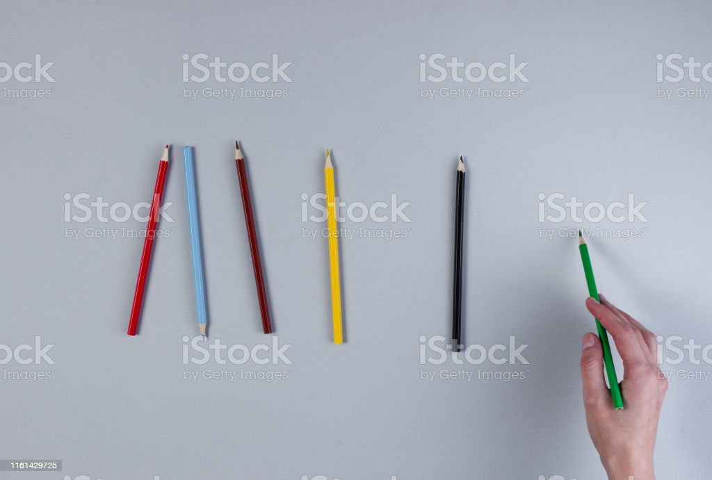 Female hand draws color pencil on gray background. top view