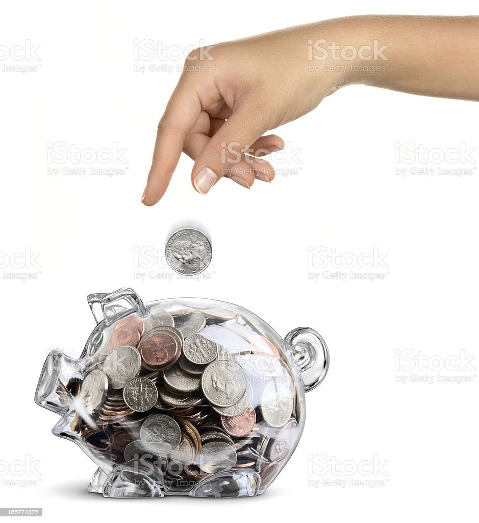 Female Hand Drops Coin Into Transparent Filled Piggy Bank Isolated royalty-free stock photo