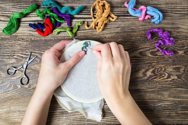 Mano femenina bordado cruzado sobre el lienzo. Hilo de rosca y mesa de madera trenzaron de algodón. - foto de stock
