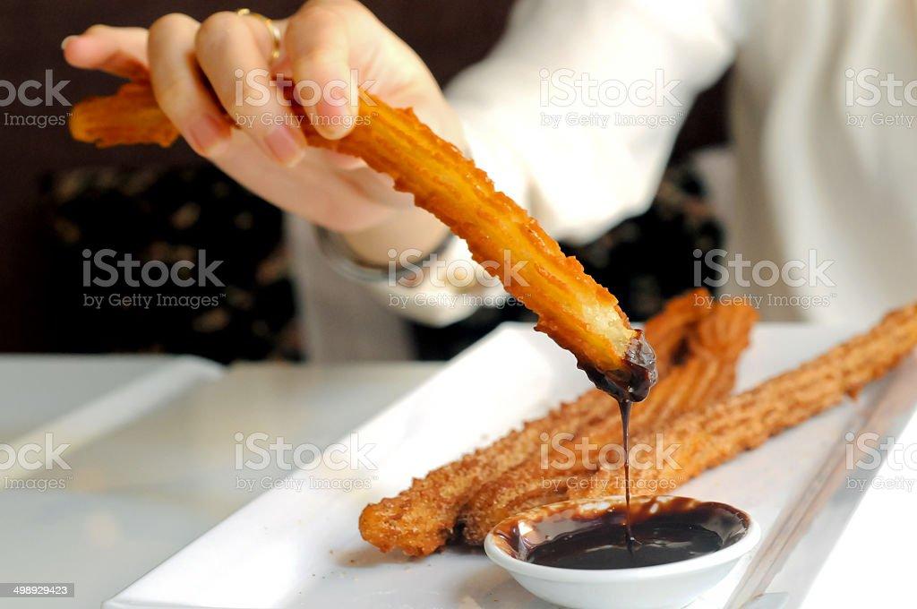 Female hand enjoying dipping Churros to dark chocolate sauce stock photo