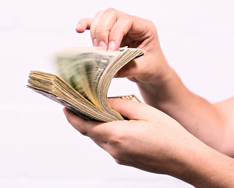 A woman's hand riffles through a thick bundle of American banknotes, creating motion blur.